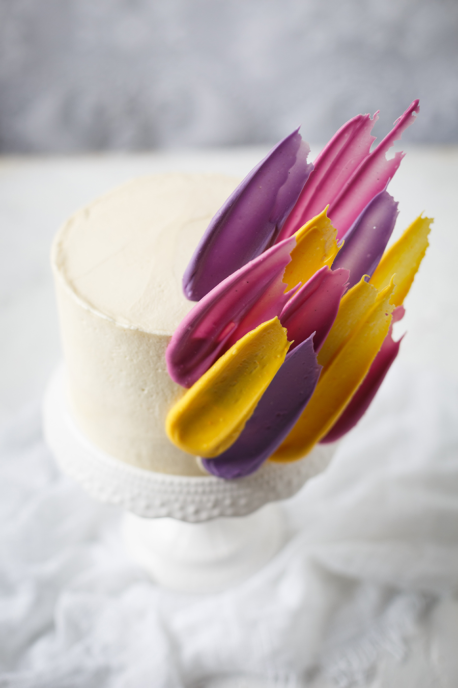 Image of a brushstroke cake - a white cake decorated with yellow, pink and purple chocoalte brushstrokes